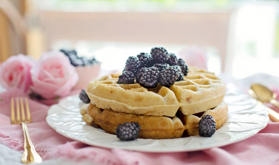 waffles with blackberry toppings on a plate, fork, spoon, tablecloth, flowers